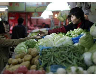 <p><b>A customer receives her change after buying vegetables at a market in central Shanghai</b> </p><p> China sought on Monday to reassure people that inflation will remain in check, voicing confidence that ample grain supplies and excess capacity