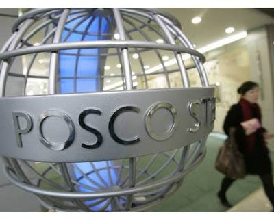 <p><b>A woman walks past a sculpture of Posco&#39;s logo at its headquarters in Seoul</b>