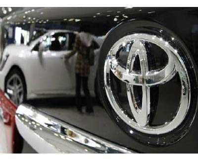 <p><b>A visitor looking at Toyota Motor's vehicles is reflected on a black vehicle at its showroom in Tokyo</b> 