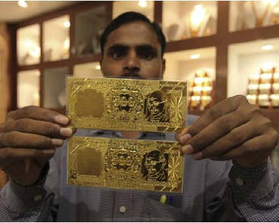 <p><b>A salesman displays gold plates in the form of the Indian rupee note at a jewellery showroom in Lucknow</b> </p><p> India wholesale gold demand retreated on Monday afternoon as stockists awaited a fall in prices and eyed the rupee for directi