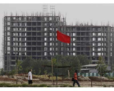 <p><b>People walk in front of a partially built residential complex on the outskirts of New Delhi</b>