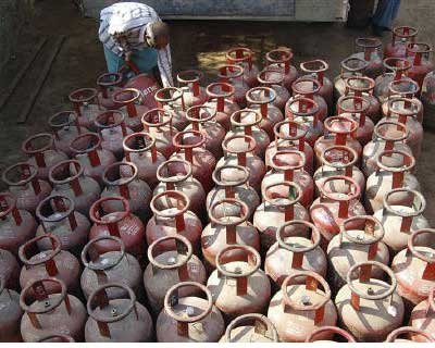 <p>A vendor loads empty Liquefied Petroleum Gas (LPG) cylinders onto a truck in Mathura