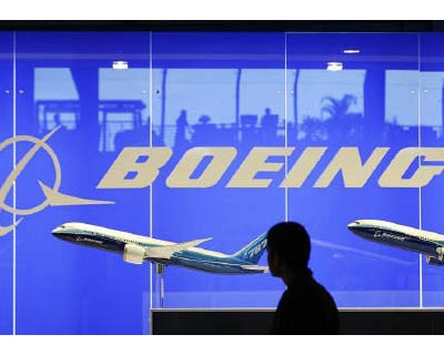 <p><b>A man looks at a scale model of Boeing&#39;s 787 dreamliner at their booth at the Singapore Air Show in Singapore</b>