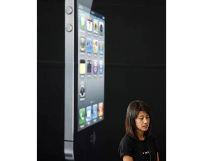 <p><b>A woman stands next to a giant advertisement for an iPhone 4 displayed at a shop in Bangkok</b>