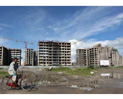 <p><b>A man rides a bicycle in front of the construction site of a residential complex in Kolkata</b>