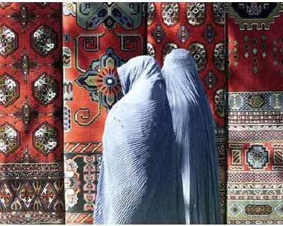 <p><b>Afghan women wearing Burqa look at carpets in Kabul November 19, 2001. In a dimly lit room at the back of an Afghan house, 21-year-old Zahara is crouched on a plank of wood weaving a large carpet on a loom that she was able to buy using a micro