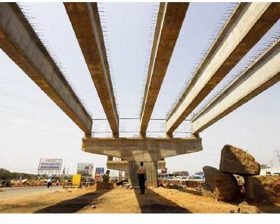 <p><b>A security guard walks under a flyover undergoing construction in Hyderabad</b>