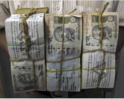 <p><b>An employee carries bundles of Indian currency notes inside a bank in Agartala, capital of Tripura</b>