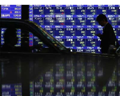 <p><b>A pedestrian and a driver pass an electronic board displaying share prices, which is reflected on a surface of a polished stone, in Tokyo</b>
