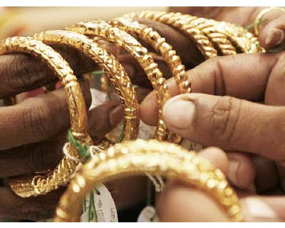 <p><b>A woman holds gold bangles at a jewellery shop in Kolkata</b>