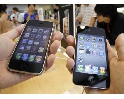 <p><b>A customer holds a new iPhone 4 (R) and an earlier version of the iPhone in a store in Tokyo.</b>  