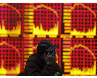 <p><b>A man reacts in front of an electronic board showing stock information at a brokerage house in Shanghai</b>