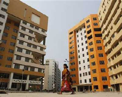 <b><p>A labourer walks past a residential estate under construction.</b>