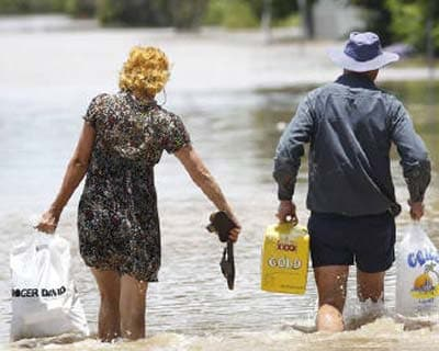 <p><b>A couple carry supplies as they walk through floodwaters in Depot Hill in Rockhampton, Queensland.</b> </p><p> Australia's record floods are causing catastrophic damage to infrastructure in the state of Queensland and have forced 75 perce