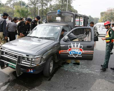 Pakistani policemen inspect a damaged police van at a shooting site in Lahore March 3, 2009. (Reuters)