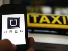 An illustration picture shows the logo of car-sharing service app Uber on a smartphone next to the picture of an official German taxi sign in Frankfurt