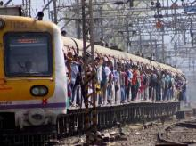 Commuters travel by a local train in Mumbai