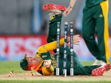 Turning Point: SA skipper AB de Villiers falls over as he fails to run out Grant Elliott (not in picture) during their World Cup semifinal against New Zealand
