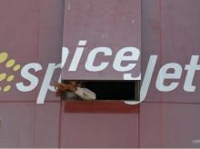 A man looks out through a window with an advertisement of SpiceJet Airline, on a commercial building in Ahmedabad