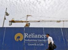 A man walks past an advertisement of Reliance Industries Limited at a construction site in Mumbai