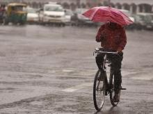 A commuter holds an umbrella while riding a bicycle during a rain shower in New Delhi