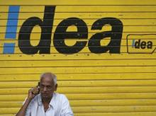 A man speaks on his mobile phone as he sits in front of a shop displaying the Idea Cellular Ltd's logo on its shutter in Mumbai