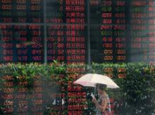 A woman walks past a window of a brokerage house with stock information reflected in it, in Shanghai. (Photo: Reuters)