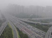 Vehicles drive along the residential buildings on Beijing's Fourth Ring Road