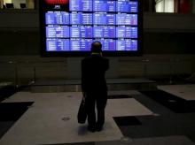 A man looks at an electronic board showing Japan's Nikkei average and related indices at the Tokyo Stock Exchange (TSE) in Tokyo