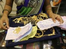 A saleswoman checks the weight and quality of gold jewellery inside a showroom in Mumbai