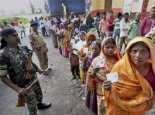 Security personnel maintaining queues of voters at a polling station during Bihar assembly elections in Begusarai on Monday. Photo: PTI