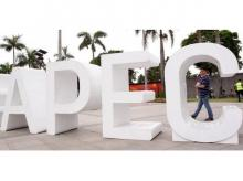 A resident carries his child past an Asia-Pacific Economic Cooperation (APEC) sign in Manila. Photo: Reuters