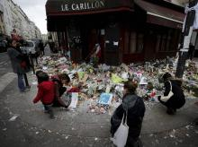 People lay flowers and candles in front of  the restaurant Le Carillon, one of the establishments targeted in Friday's gun and bomb attacks, in Paris