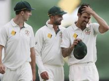 Australia's retiring test crickter Mitchell Johnson, right, and team mates Nathan Lyon, centre, and Mitchell Marsh leave the ground on a rain delay against New Zealand during their cricket test match in Perth, Australia. File photo: PTI