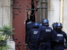 French police officers storm a church after a raid in Paris suburb Saint-Denis
