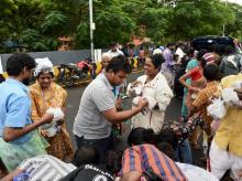 People rescued at waterlogged houses of Kotturpuram, receiving food packets while sheltering at a road following rains in Chennai