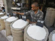 A vendor arranges price tag over sack filled with sugar at wholesale vegetable market in Ahmedabad