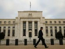 A man walks past the Federal Reserve in Washington