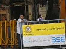 A man looks at a screen across the road displaying the Sensex on the facade of the Bombay Stock Exchange (BSE) building in Mumbai