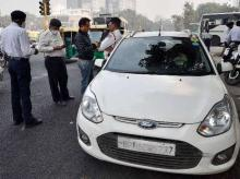 Traffic police men slap a challan to a commuter for riding with number plate ending with an odd digit as the trial of the 'odd-even car scheme' is operational at ITO in New Delhi. Photo: PTI
