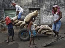 Labourers unload sacks of rice from a handcart at a wholesale market in Kolkata
