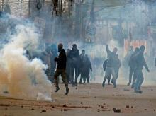 Angry youth throwing stones on police amid tear gas smoke fired by police to disperse them during clashes on Srinagar-International Airport Road at Peerbagh in Srinagar.