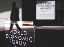 A man passes a logo during the annual meeting of the World Economic Forum (WEF) in Davos, Switzerland