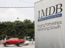 Traffic passes a 1Malaysia Development Berhad (1MDB) billboard at the Tun Razak Exchange development in Kuala Lumpur, Malaysia
