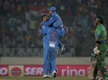 India's Yuvraj Singh, left, celebrate with his teammates after the dismissal of Pakistan's Umar Akmal, right, during the Asia Cup Twenty20 international cricket match between them in Dhaka