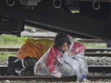 Migrant children cross railway tracks under a freight train during rainfall at the northern Greek border station of Idomeni