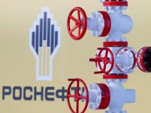 The logo of the Russian state oil company Rosneft is pictured behind a pipe at the Samotlor oil field outside the West Siberian city of Nizhnevartovsk, Russia