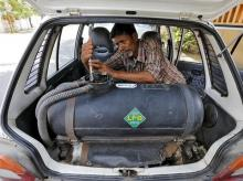 A mechanic repairs a pipe of a LPG tank installed in a car outside his workshop in Ahmedabad. Photo: Reuters