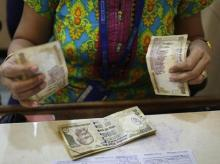 cashier counts rupee notes inside a bank in Mumbai