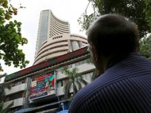 A man looks at a screen across a road displaying the Sensex on the facade of the Bombay Stock Exchange (BSE) building in Mumbai